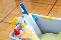 close up of cleaning equipment in a bucket for house and home cleaning on a wooden parquet floor