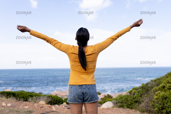 Fit african american woman standing spreading arms in mountain countryside