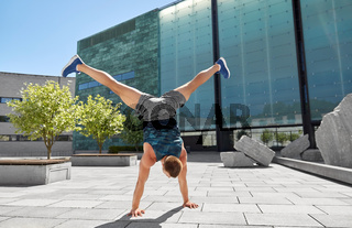 young man exercising and doing handstand outdoors