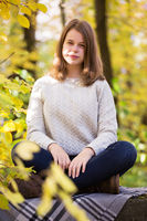 Teenage girl sitting in autumn garden