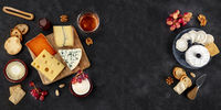 Cheese panorama. Goat cheese, Brie, blue cheese and others, shot from the top on a black background with a place for text