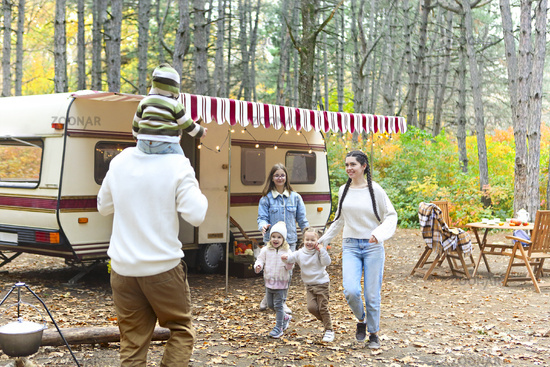 Young smiling family while hugging near house on wheels outdoors