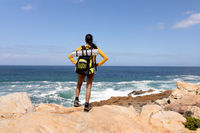 Fit afrcan american woman wearing backpack hiking on the coast