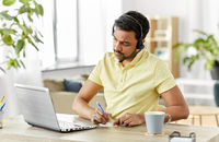 indian man with headset and laptop working at home