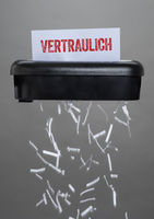 A shredder destroying a document - Confidential - Vertraulich German