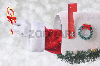 Santa Claus arm holding a candy cane coming out of a mail box with silver bokeh background and snow effect.