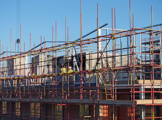 building workers in protective clothing on scaffolding on a residential constriction site in the center of york