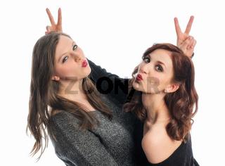 zwei freundinnen albern herum und zeigen victory