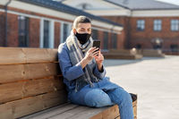 woman in face mask with smartphone in city