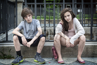two dirty urban teens sitting on a wall