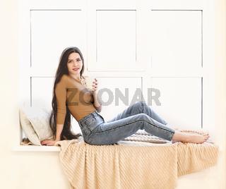 Young woman drink tea on windowsill