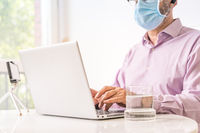 Man working with computer and surgical mask.