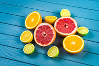 juicy oranges, grapefruits, limes and lemons lie on a blue wooden table