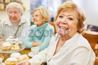 Glückliche Seniorin mit Freunden beim Kuchen essen und Kaffee trinken im Altenheim