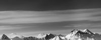 Black and white panoramic view on snowy mountains in winter