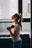 Slender athletic girl performs physical exercises with dumbbells.