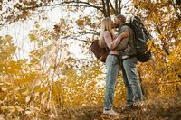 Young Couple Of Tourists Kissing in Forest Outdoors