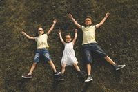 two brothers and a sister lie on the grass with their arms and legs outstretched. asian appearance