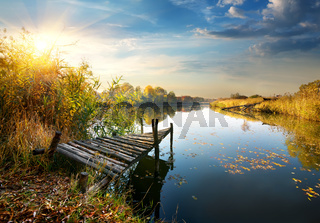 Old pier on autumn river