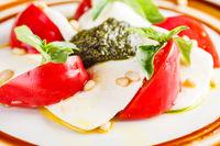 Caprese salad with mozzarella, tomato, basil and pesto