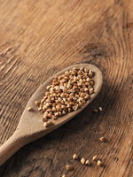 Buckwheat on a wooden spoon on a wooden kitchen table