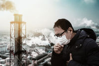 man wearing mask against smog  and  air pollution factory background