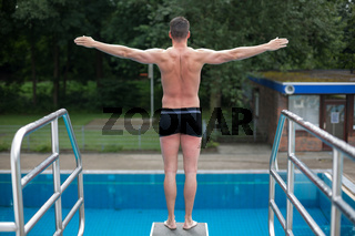 Man ready to jump from diving board at swimming pool