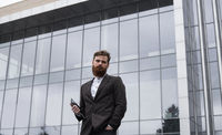 Modern Young bearded Business man standing with a digital tablet. Young hipster businessman holding tablet in hands outdoor. Working online with a tablet while standing outside on an office building.
