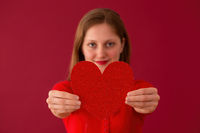 Blurred female showing heart to the camera on red background