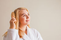 Profile of beautiful young woman brushing her blonde healthy hair