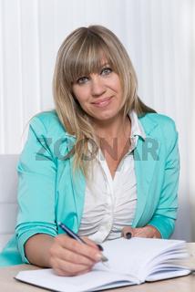 Geschäftsfrau schreibt in Terminkalender