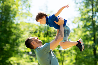 happy father with son playing in summer park
