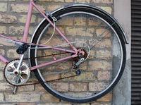Wheel of  broken pink women's  bike hanging on a yellow brick wall