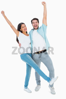 Happy casual couple cheering together