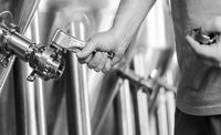 brewer operating industrial beer brewing equipment in brewery interior