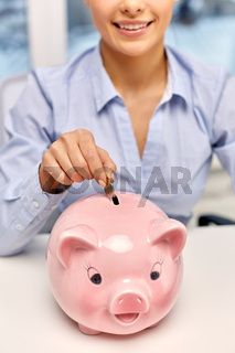 businesswoman with piggy bank and coin at office
