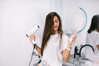 Young beautiful woman in the bathroom holding a hairdryer and a small bottle