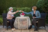 Seniorin und Tochter mit Mundschutz beim Kaffee trinken im Garten