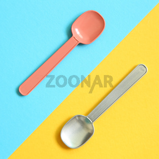 Pink and silver spoon on blue and yellow background