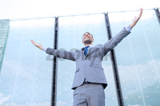 young smiling businessman over office building