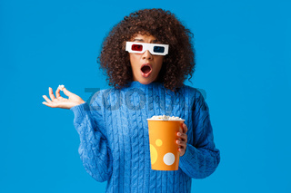 Shocked and startled young cute african-american hipster girl watching action movie, drama gasping and drop jaw as eating popcorn and see shocking scene in film with 3d glasses, blue background
