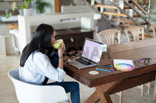 Mixed race woman drinking coffee using laptop by table at home