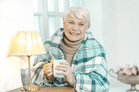 Smiling Old Lady Wrapped In A Checkered Plaid Is Holding A Cup Of Tea.