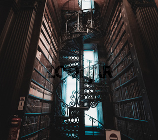 DUBLIN, IRELAND, DECEMBER 21, 2018: Magnificent spiral staircase in The Long Room in the Trinity College Library, home to The Book of Kells, full of details and ornamented.