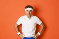 Concept of workout, sports and lifestyle. Portrait of startled middle-aged fitness guy in activewear, drop jaw and looking at camera amazed, standing over orange background