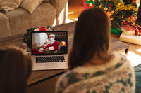 Rear view of woman and son having a videocall with santa claus wearing face mask on laptop at home