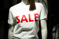 Female upper body dummy in a shop display with the word SALE written on it. Consumerism and low price concept.