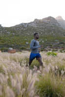 Fit african american man in sportswear running through tall grass