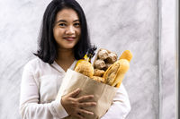 Portrait Asian housewife woman hold grocery bread bag.