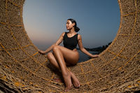 Beautiful girl on the straw nest over sea and sky background during sunset
